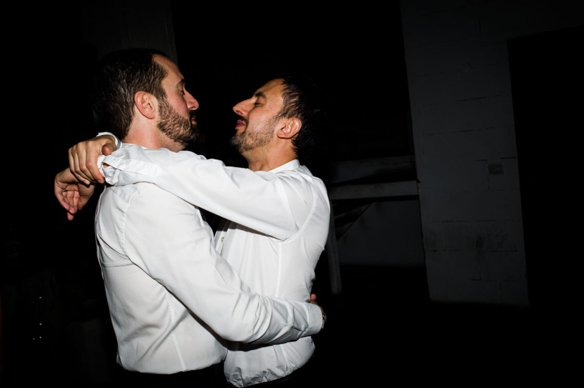 printed photograph of two bearded boys with protruding noses with closed eyes embraced wearing a white blouse