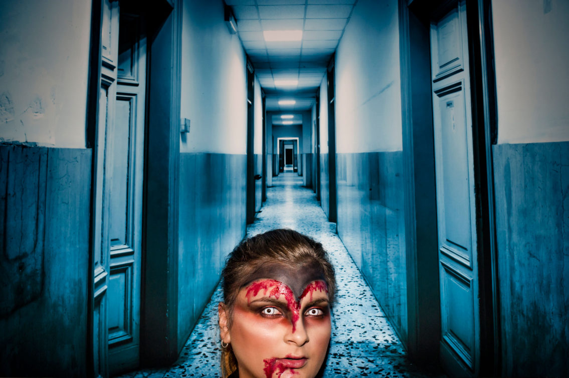 printed photograph of a woman wearing blood and contact lenses in the background of a magenta corridor