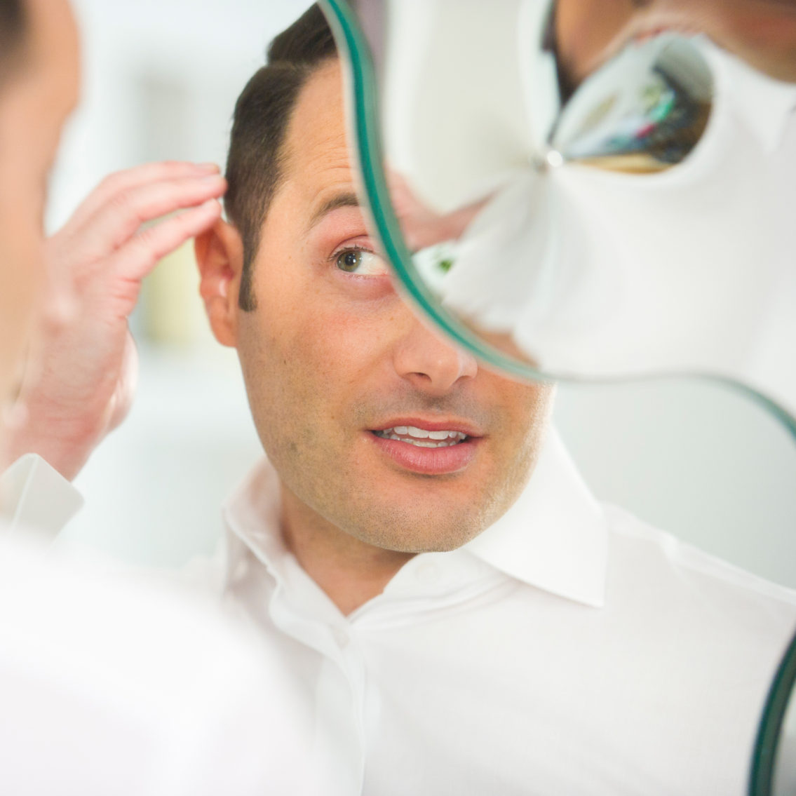 photograph of a man looking in the mirror and fixing his hair