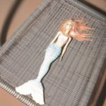 photograph of barbie's little mermaid toy on a plastic chair