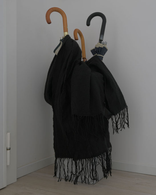 photograph of a black scarf resting on an umbrella stand with 3 umbrellas